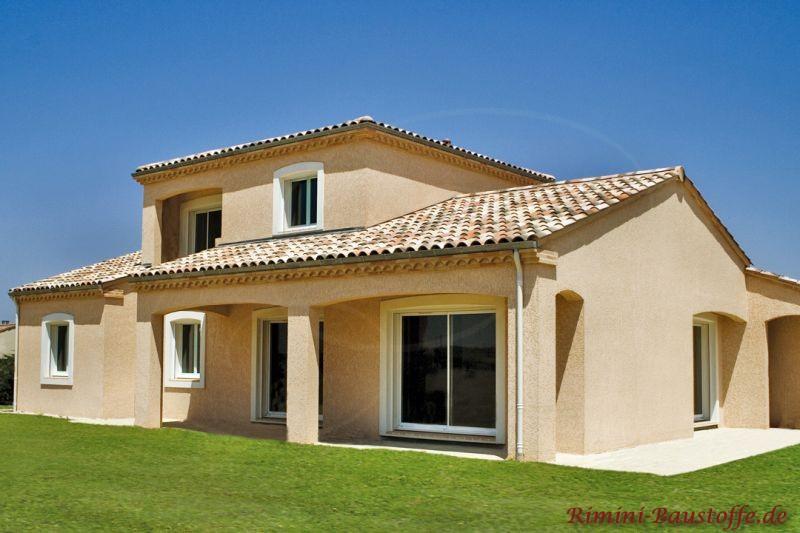 schönes Einfamilienhaus mit überdachter Terrasse im südländischen Stil mit hellem Putz und schönem mediterranen Dach