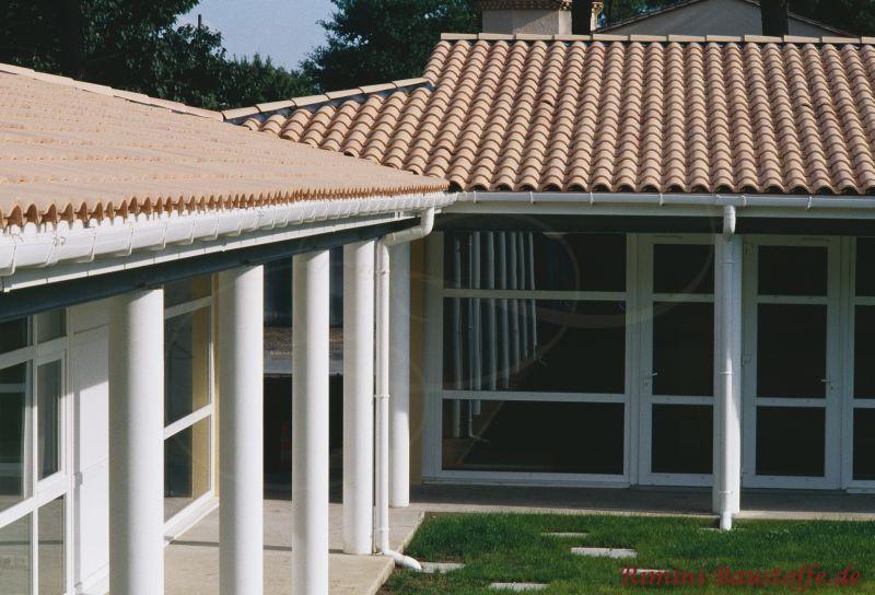 mediterranes Wohnhaus mit vielen großen Fenstern, weißen runden Pfeilern und einem schönen milden Dach