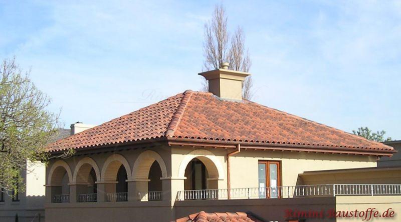schönes Gebäude im mediterranen Stil durch die runden Bögen und dem roten Dach zur hellen Putzfassade