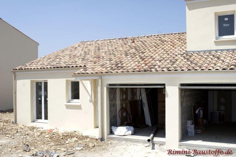 Neubau im mediterranen Stil durch doe helle Putzfassade und dem changierenden hellbraunen Dach
