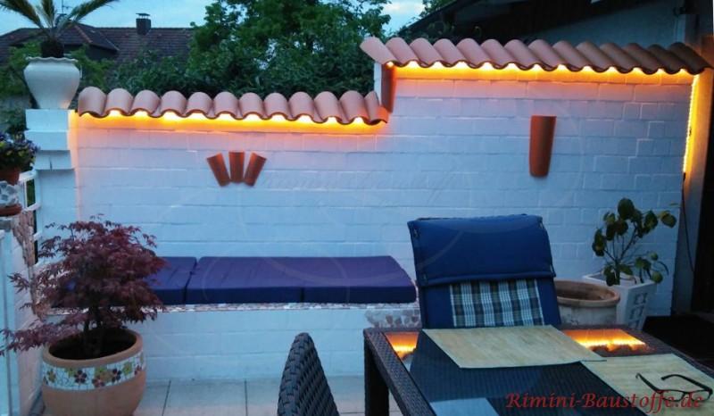 weiss gestrichene Gartenmauer mit Halbschalen und Beleuchtung