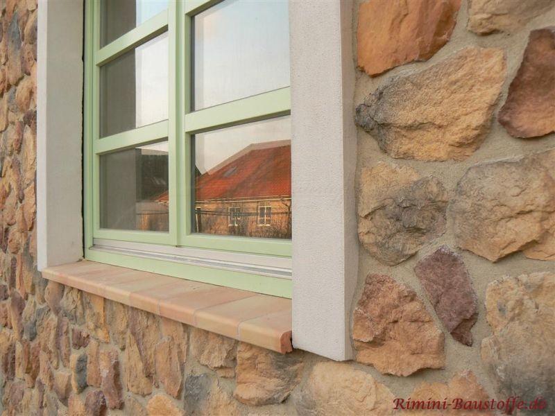 Tonfensterbank zu einem gruenen Fenster