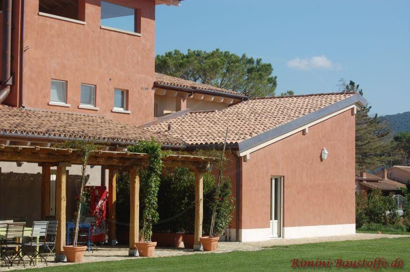 rote Putzfassade und Pultdach mit Halbschalen eingedeckt