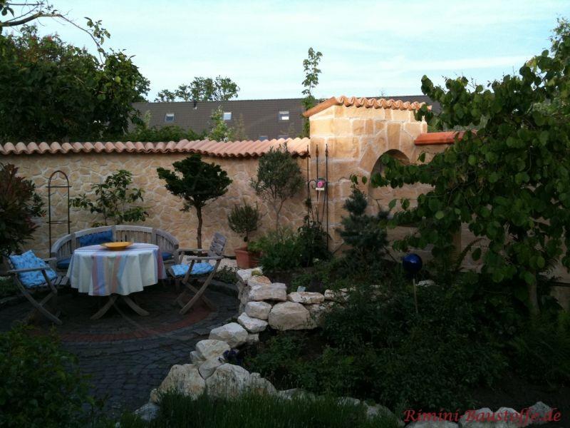 Sitzecke im Garten umrandet von einer Natursteinmauer mit mediterraner Mauerabdeckung aus Halbschalen