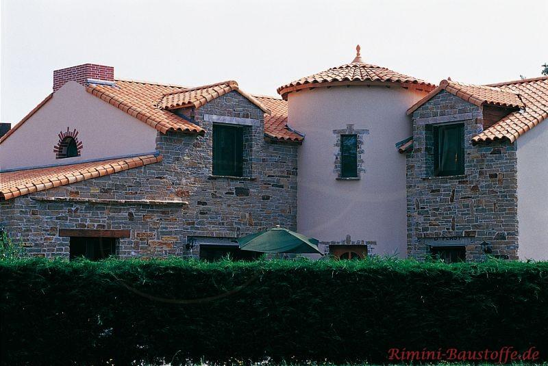 sehr ausgefallene Architektur mit eingefassten runden Türmen und Natursteinwand