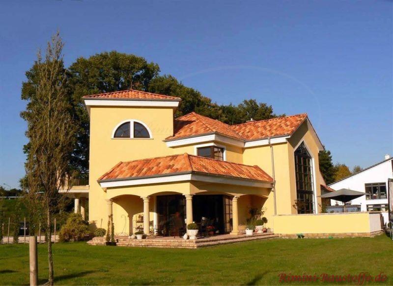 mediterrane Villa mit hellgelber Fassade, halbrunden Fenstern und typischen Pfeilern