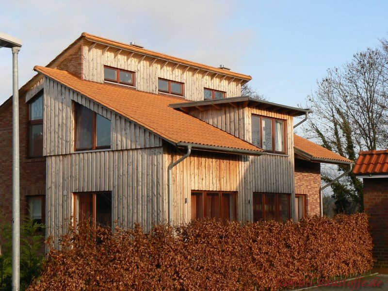 ausgefallene Architektur mit Pultdächern und einer Holzfassade, dazu passend ein schöner rötlicher Ziegel