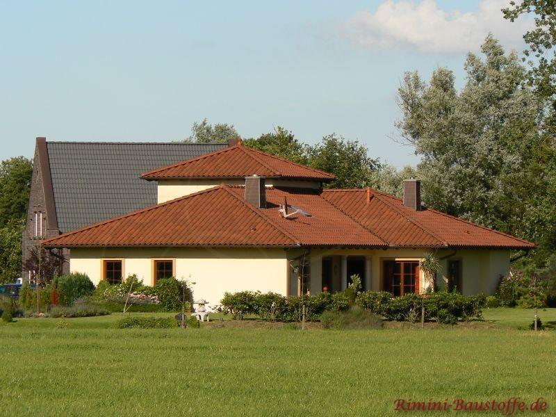Haus im mediterranen Stil mit heller gelber Putzfassade und schönem kräftig rotem Dach