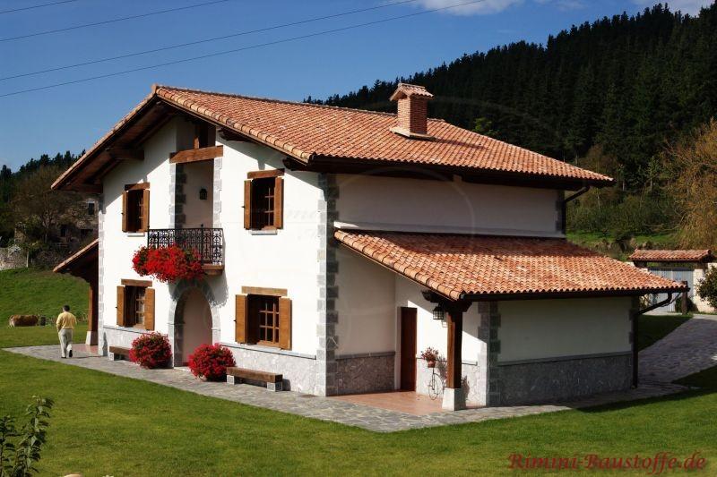 Haus in Österreich mit Natursteinsockel, weißer Putzfassade und Holzfenstern
