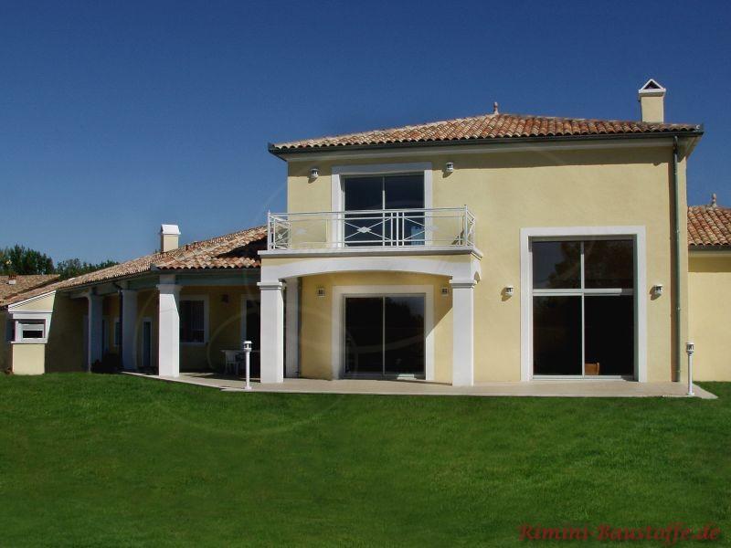 mediterranes Wohnhaus mit hellgelber Putzfassade, weißen Pfeilern und weißen Faschen