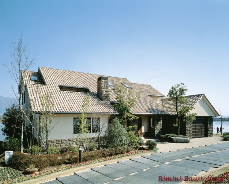 kleines Einfamilienhaus mit weißer Putzfassade und schönem Dach in Braun- und Erdtönen