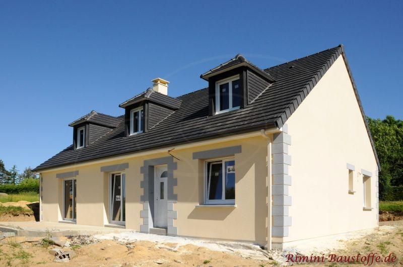 Neubau mit hellgelber Putzfassade und schönem dunklen Dach mit Gauben