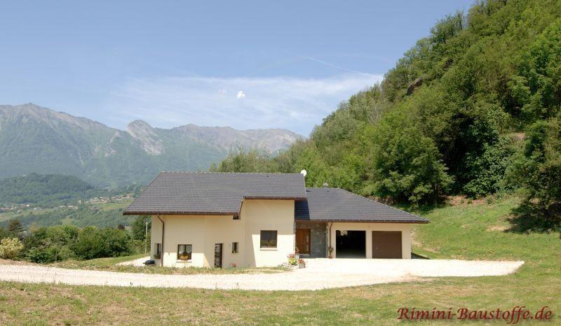 kleines Wohnhaus im Grünen mit hellgelber Putzfassade und dunklem antrazithfarbenem Dach