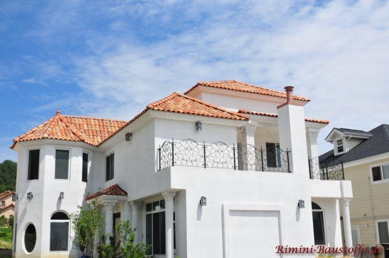 schönes helles Wohnhaus mit strahlend weißer Putzfassade und südländischen Dachziegeln