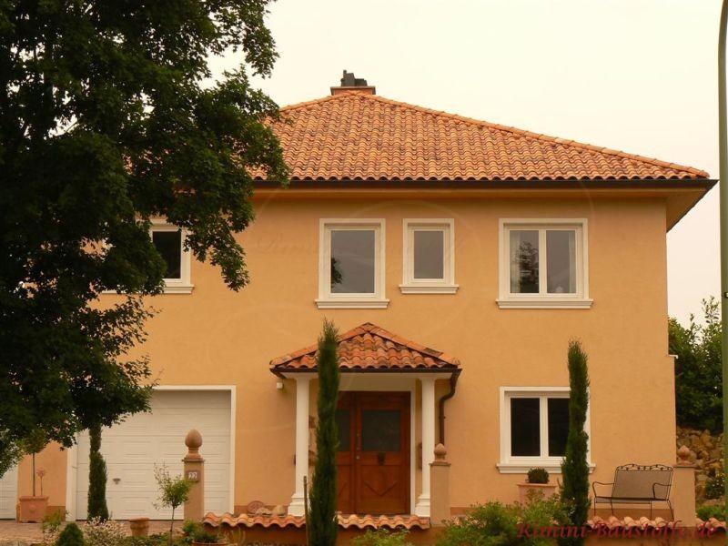 gelbe Putzfassade mit weißen Faschen und einem passenden Dach in Rottönen