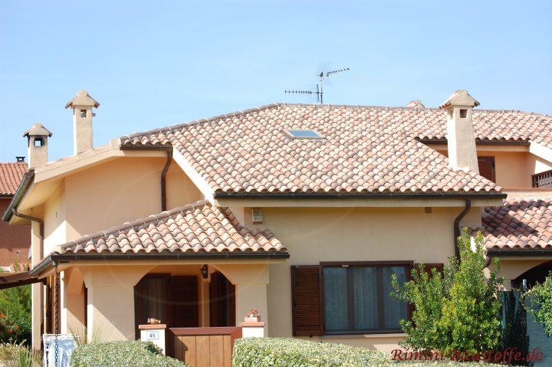 sehr schönes Haus im südländischen Stil mit hellgelber Putzfassade, dunklen Holzfenstern und einem hellen braunen Dach