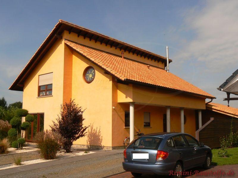 strahlend gelbe Putzfassade mit rundem Fenster und Pultdach