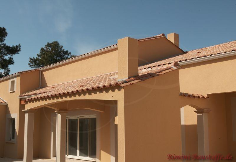 mediterrane Finka mit orangefarbener Putzfassade und schönen weißen Fensterrahmen, dazu passend ein Satteldach mit südländischen