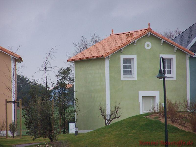 kleines Reihenhaus mit hellgrüner Putzfassade und weißen Fensterrahmen, dazu passend ein rötliches Satteldach