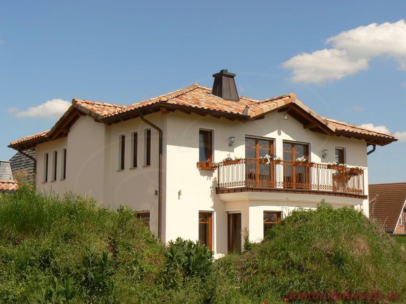 große mediterrane Villa mit schöner heller Putzfassade und dunklen Holzfensterrahmen und Balustraden