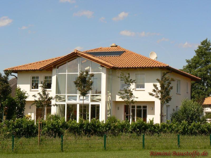 große lichtdurchflutete Villa mit großer Fensterfront und sehr schönem rötlichen Walmdach