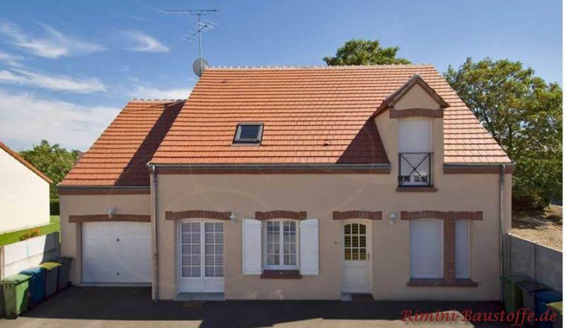Einfamilienhaus mit heller Putzfassade, dunkleren Faschen und schönen weißen Fenstern