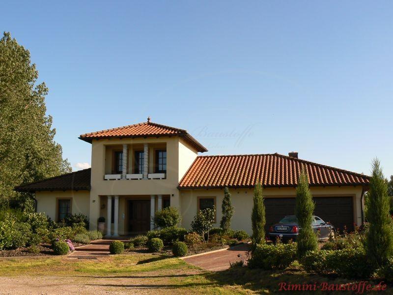 wohnhaus mit heller Putzfassade und schönem großen offenen Eingangsbereich, passend zu den Fenstern ein rotes Dach