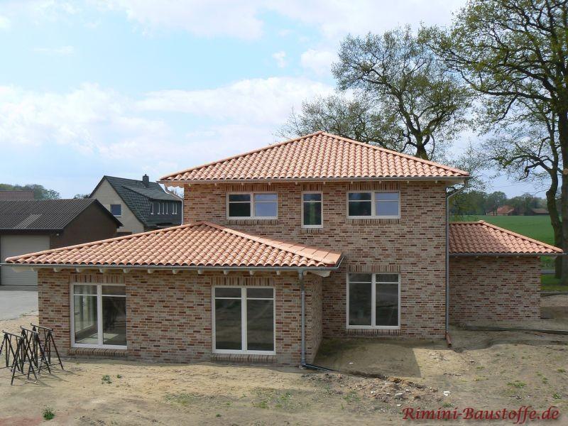Klinkerbau mit weißen Fenstern und passendem rot changierendem Dach
