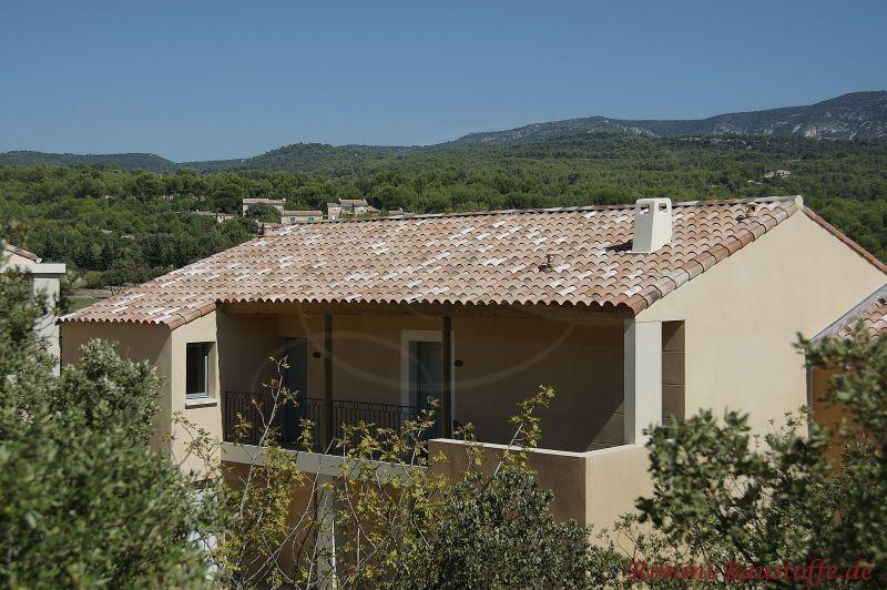südländisches Wohnhaus im Grünen mit heller sandfarbener Putzfassade und einem passenden bräunlichen Dach