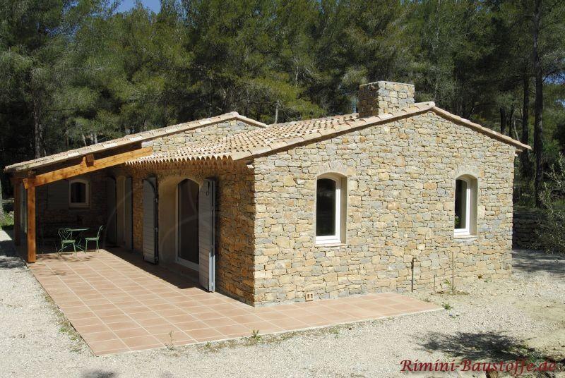 Wohnhaus mit Natursteinfassade, weißen Fenstern und farblich passendem Satteldach