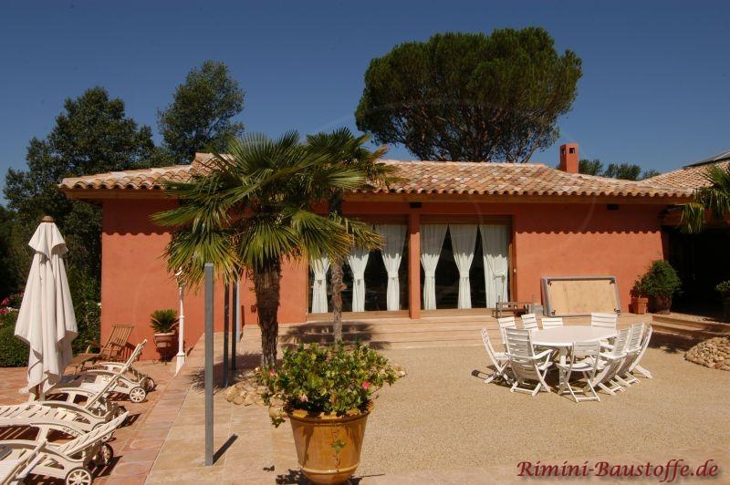 Ferienhaus mit strahlender roter Putzfassade und schönem Garten