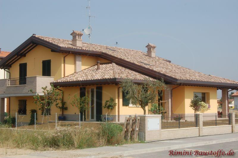 Gebäude mit heller gelber Putzfassade und sehr schönem passenden Satteldach in hellen Brauntönen