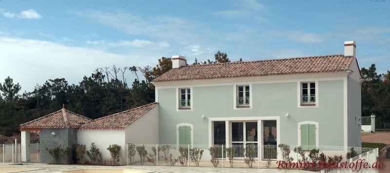 schöne mintgrüne Putzfassade mit weißen Sprossenfenstern und einem großen Terrasseneingang. Dazu eine dunkelrote Dachfläche