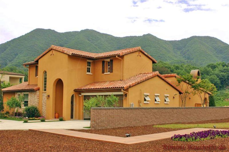 schöne kräftige gelbe Putzfassade zu einer rötlichen Dachfläche und südländischer Architektur
