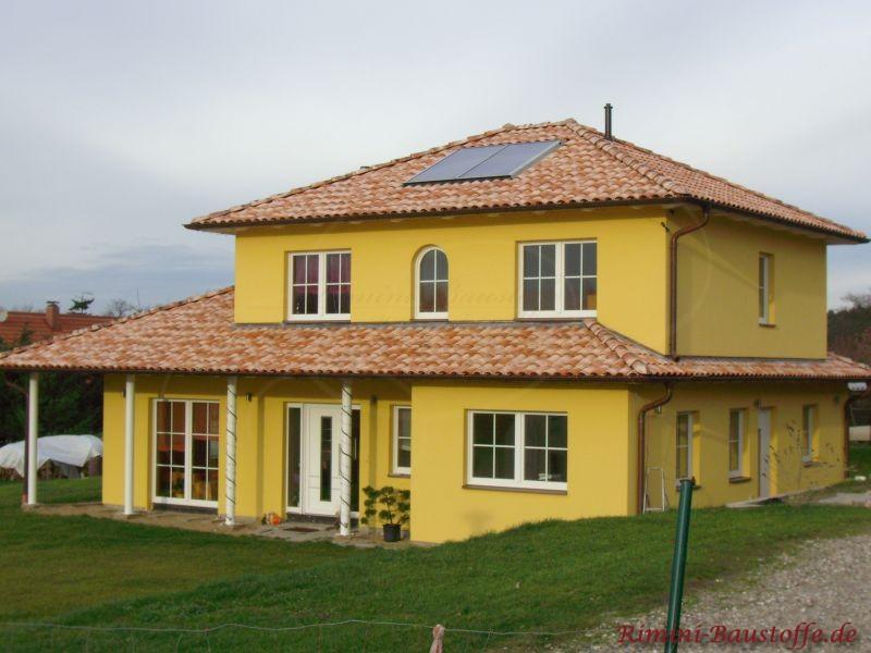 zitronengelbe Putzfassade mit weißen Fenstern und einer schönen Dachfarbe, die mit dem Gesamteindruch harmonisiert