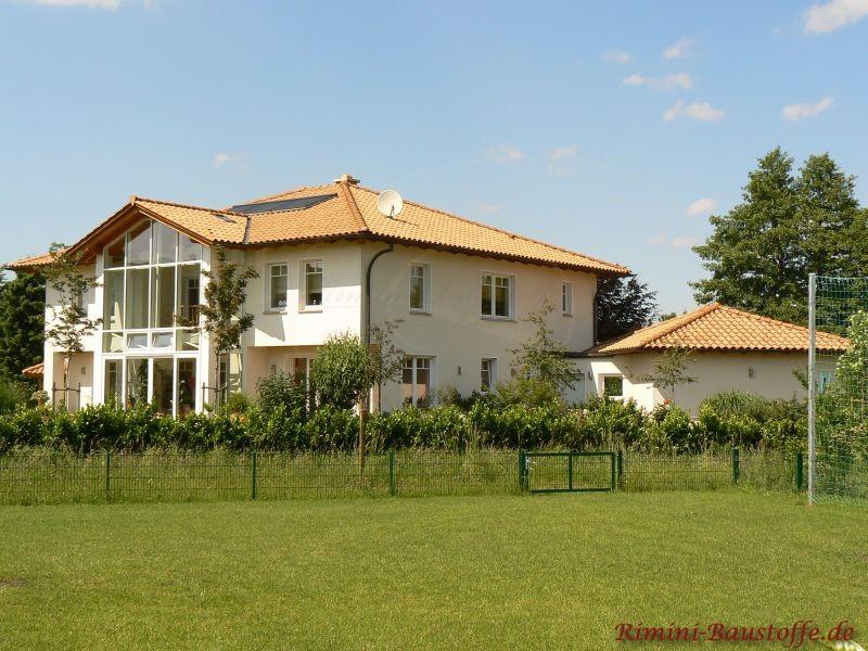 große Villa mit hoher Fensterfront, die für viel Licht sorgt