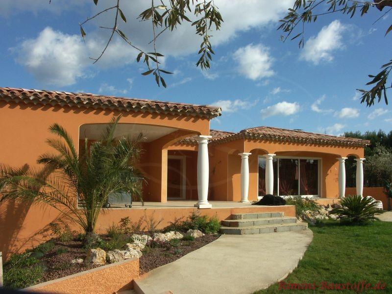kräftige orange Putzfassade mit weißen Pfeilern und einem sehr schönen mediterranen Garten