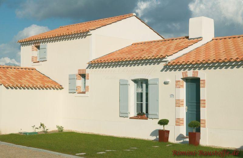 kleines südländisches Haus mit hellgelber Putzfassade und hellen Fensterläden. Dazu eine kräftigere Dachfarbe in Rottönen