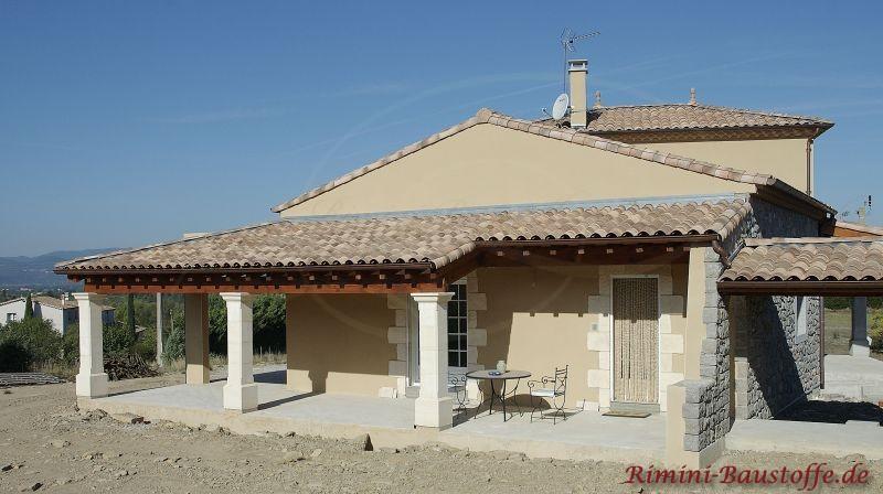 schönes Einfamilienhaus im mediterranen Stil mit Kies im Garten passsend zur Dachfarbe