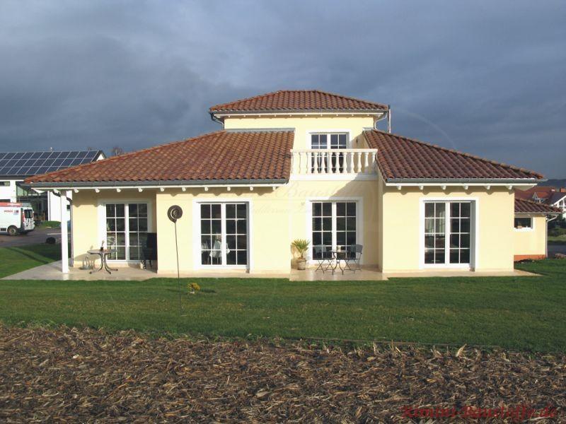 schönes südländisches Einfamilienhaus mit großen weißen Sprossenfenstern und einer kräftig roten Dachfläche
