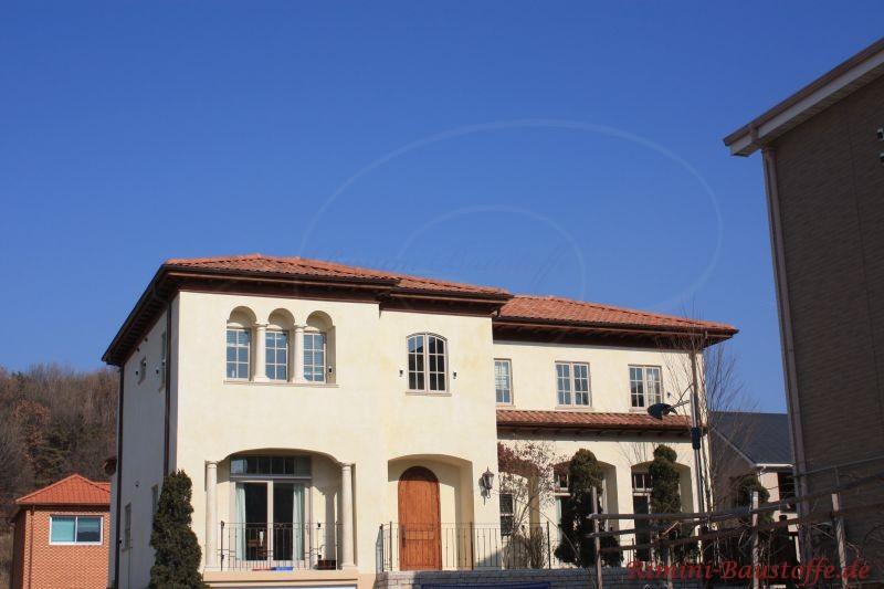 schönes traditionelles südländisches Gebäude mit heller Putzfassade und einem Pultdach in einem kräftigen Rot