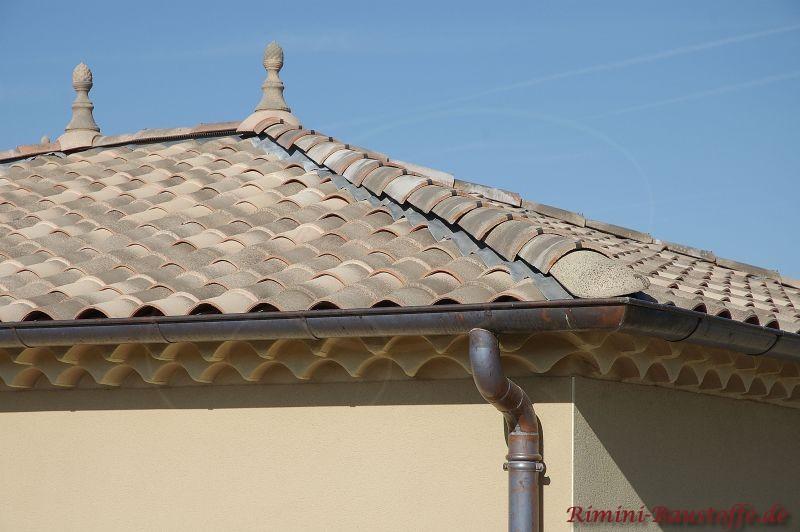 hellgelbe Puzfassade mit schönen hellen braun-grauen Dachziegeln und Zierspitzen