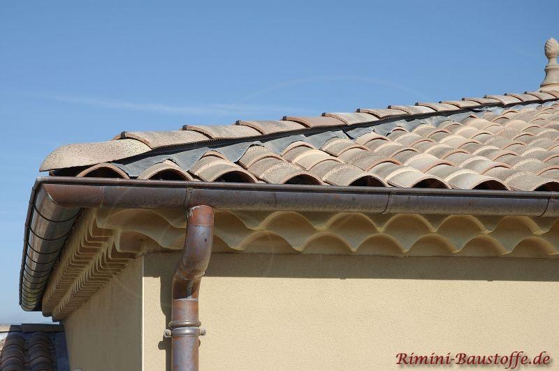 Ansicht einer Traufe an einem hellen Putzbau mit hellem braunen Dach