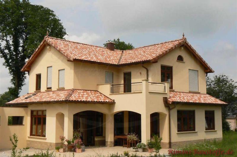 sehr schönes Einfamilienhaus im südländischen Stil mit heller gelber Putzfassade und schönen dunkelbraunen Holzfenstern
