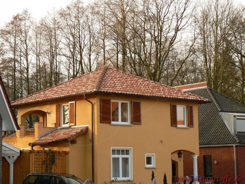 schönes südländisches Einfamilienhaus mit heller gelber Putzfassade, dunkelbraunen Holzfenstern und passendem mediterranem Dach