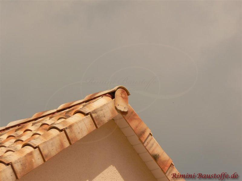 Nahaufnahme eines Giebels mit schönen Ortgangziegeln und runder Firstscheibe