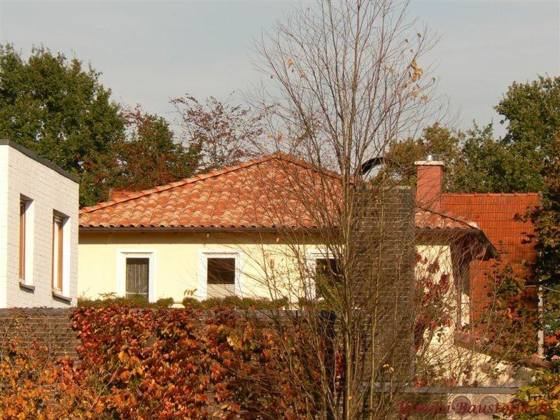 kleiner mediterraner Bungalo mit heller Putzfassade und schönem kräftigen roten mediterranen Dach