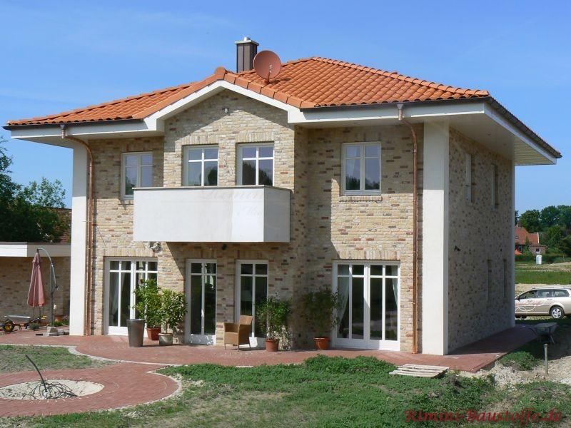 sehr schöne helle Klinkerfassade mit weißen Putzelementen und schönem roten Dach