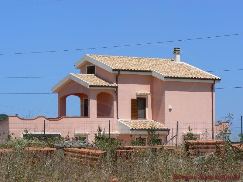 hohes Gebäude mit hellrosa Putzfassade und schönem passendem mediterranen Dach