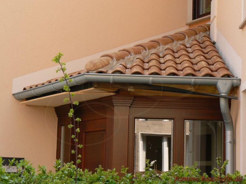 kleiner Erker mit dunkler Holzverkleidung an einem Haus mit heller Putzfassade